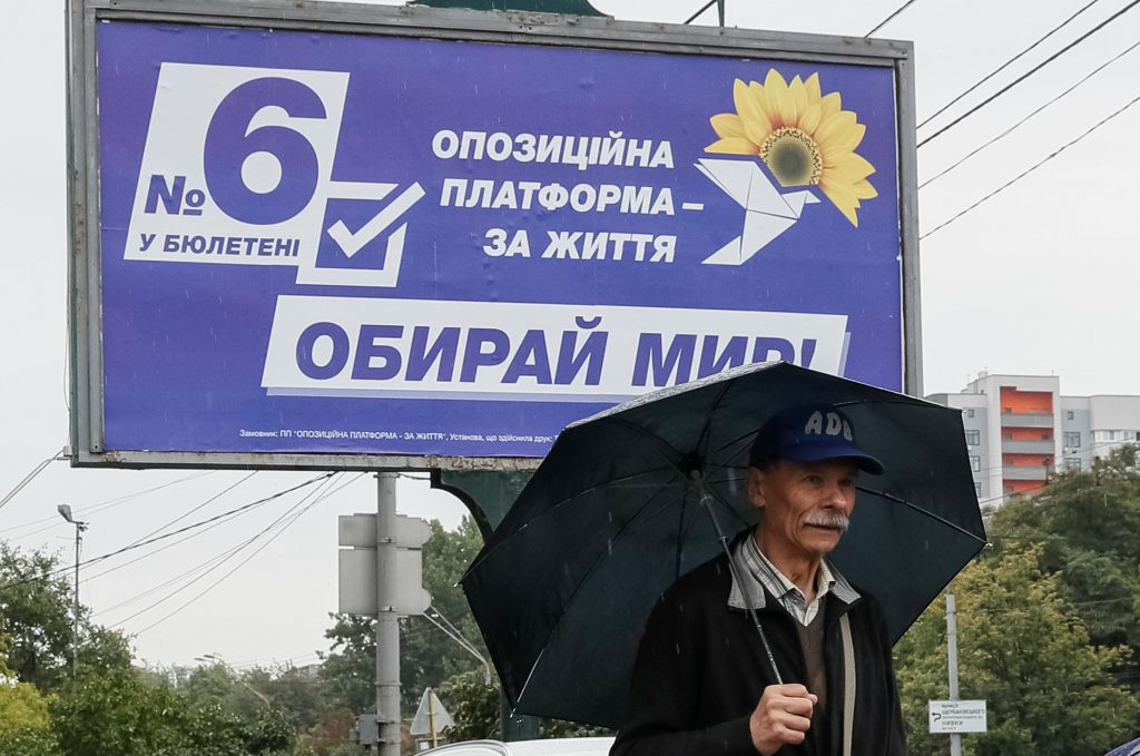 A man walks past an election campaign poster of Ukrainian Opposition Platform - For Life political party in Kyiv, Ukraine July 15, 2019. REUTERS/Gleb Garanich