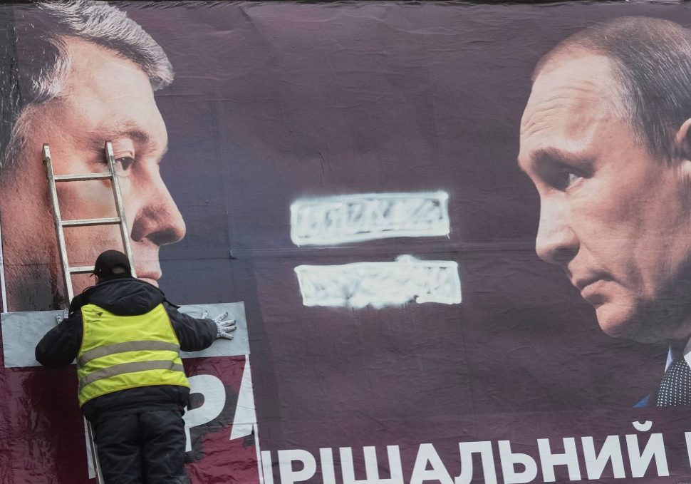A municipal worker removes an election poster of Ukrainian President and presidential candidate Petro Poroshenko and Russian President Vladimir Putin in Kyiv, Ukraine April 13, 2019. Picture taken April 13, 2019. REUTERS/Gleb Garanich